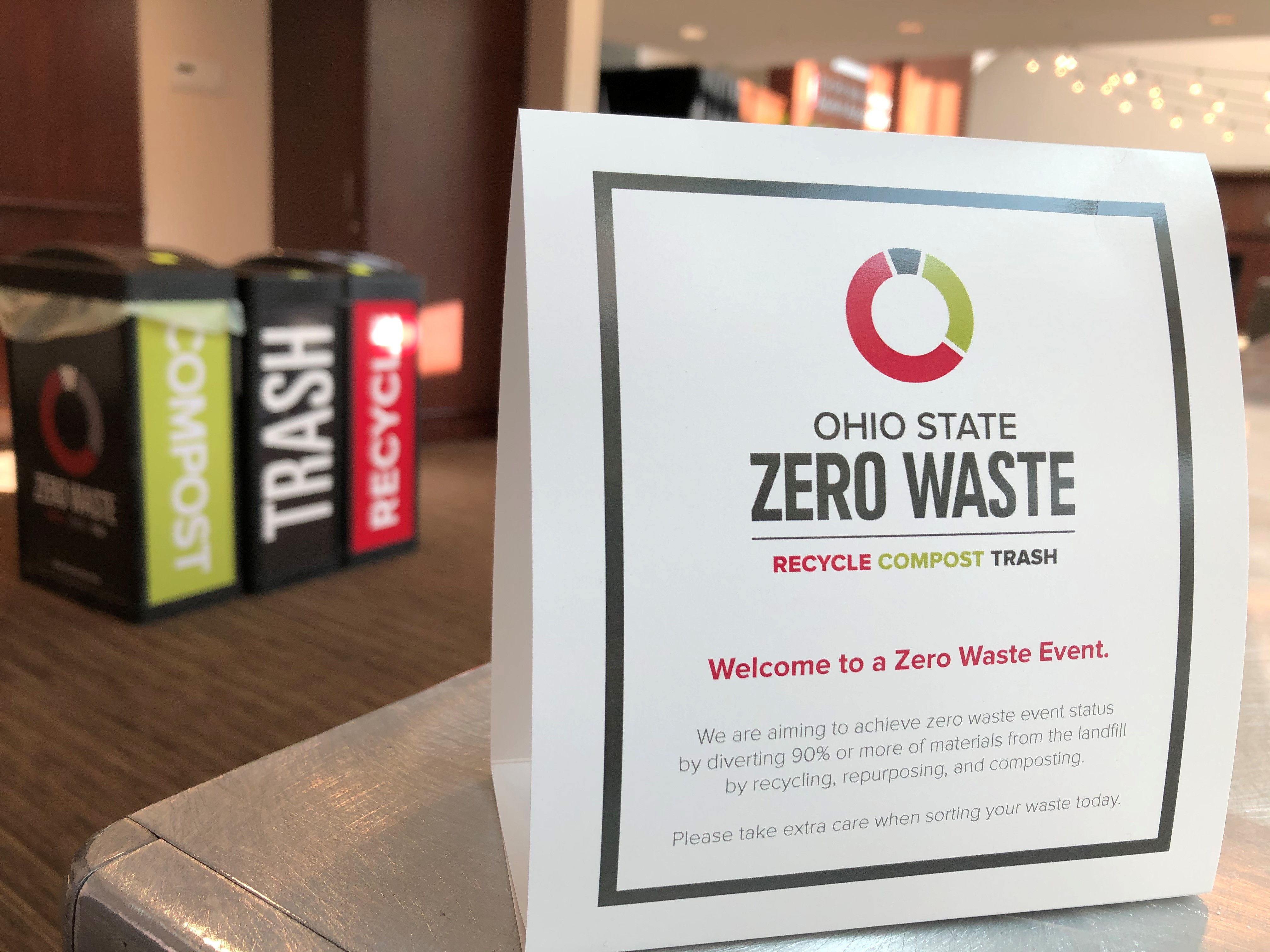 zero waste bins blurred in the background, with table placard in the foreground